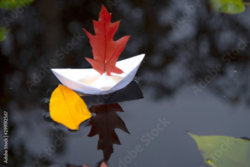 A white paper boat with an oak leaf instead of a sail on black water Canvas Print