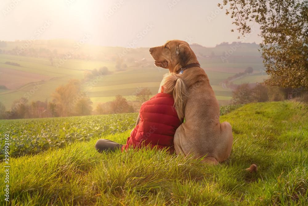 Fototapeta Beste Freunde - ein Kind lehnt sich an seinen Hund, einen Broholmer, an und beide genießen in der Natur den Sonnenuntergang an einem Herbsttag