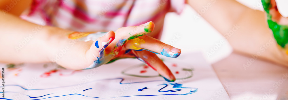 Fototapeta Close up young girl painting with colorful hands. Art,  creativity and painting concept. Horizontal image.