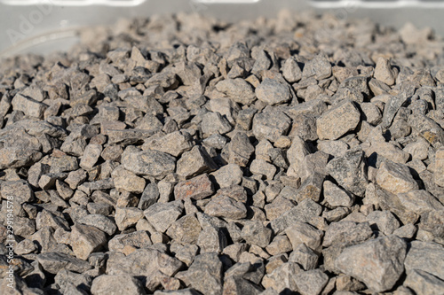 Fototapeta A large pile of bulk 57 gravel sits ready to be used on a job site for a DIY hom