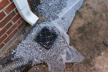 Plastic Catch Basin Installed Under A Downspout To Alleviate Drainage Issues Against A Red Brick Home