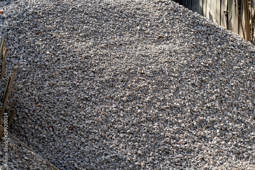 Fotografie, Obraz A large pile of bulk 57 gravel sits ready to be used on a job site for a DIY hom