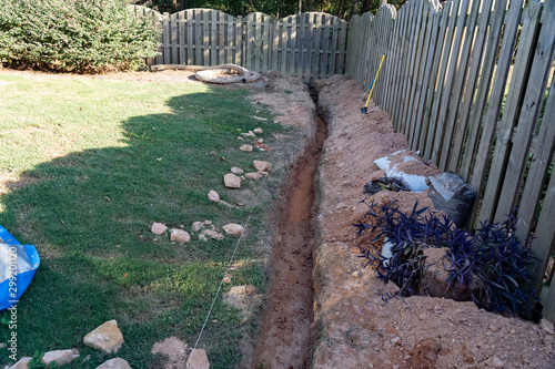 A trench is dug as the first step of a DIY French drain home improvement project to alleviate drainage issues Canvas Print