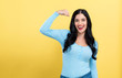 Powerful young woman in a success pose on a yellow background