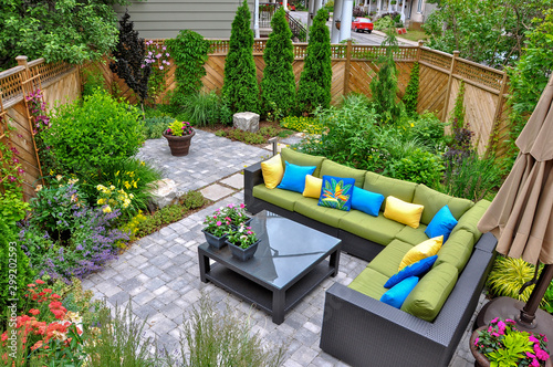Fototapeta A beautiful small, urban backyard garden featuring a tumbled paver patio, flagstone stepping stones, and a variety of trees, shrubs and perennials add colour and year round interest.  obraz