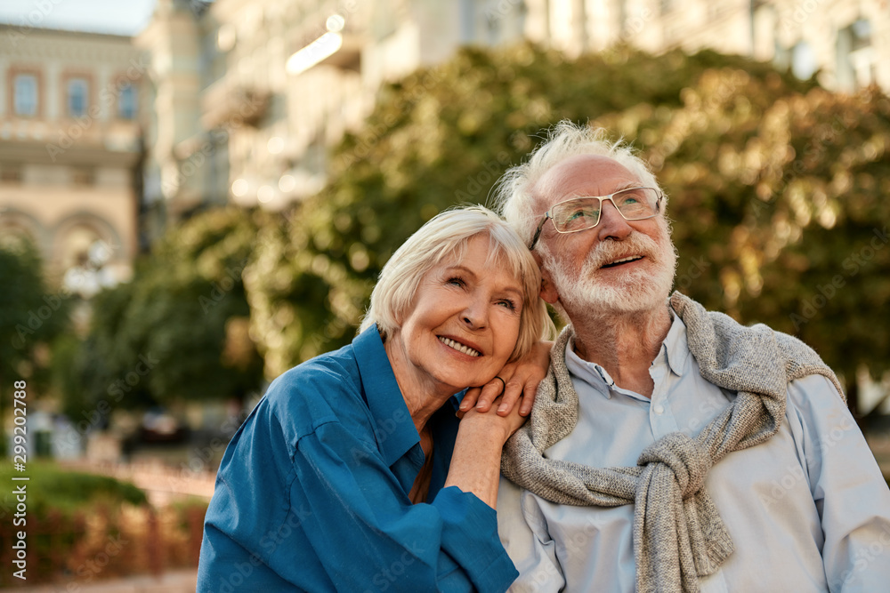 Fototapeta Endless love. Portrait of beautiful senior woman leaning at shoulder of her husband and smiling while spending time together outdoors on a sunny day