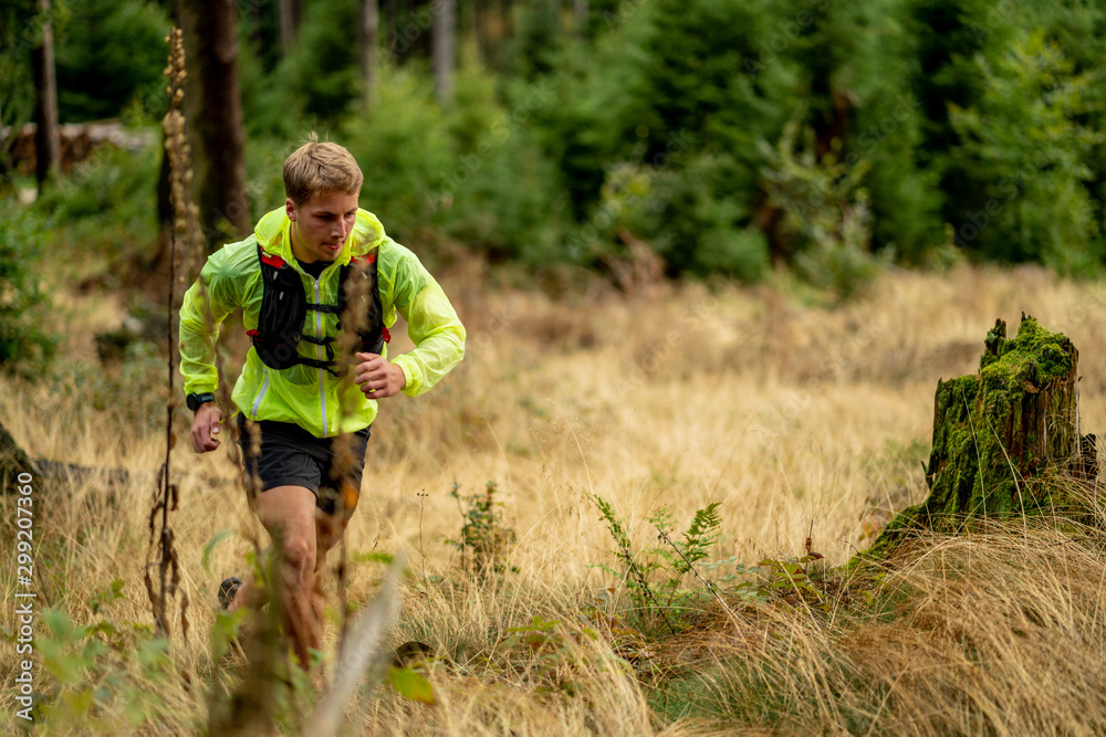 Fototapety, obrazy: Young athlete runs uphill with a drinking backpack. Trail run in a beautiful autumn forest