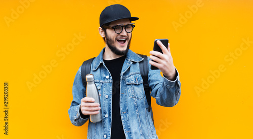 Portrait of young happy hipster man on orange background Fotobehang