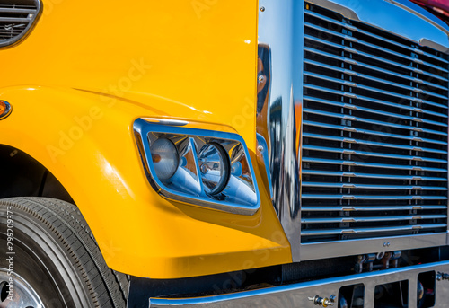 Obraz Part of yellow big rig semi truck with chrome grille and headlight with reflection of sunlight - fototapety do salonu