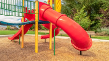 Panorama Frame Close Up View Of The Colorful Playground With Red Closed Tube Slide At A Park