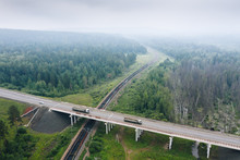 """Crossing Of Highway R-255 """"Siberia"""" Over Road Bridge With Trans-Siberian Railway In Green Taiga Forest, Smog From Fires In Air, Aerial View. Main Freight Traffic Routes. Krasnoyarsk Krai, Russia."""