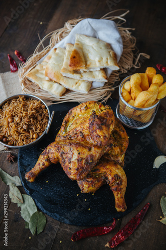 Photo Tandoori spiced chicken served with rise, chips and naan