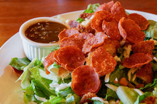 Fried Pepperoni On Top Of A Salad With A Side Of Balsamic Dressing