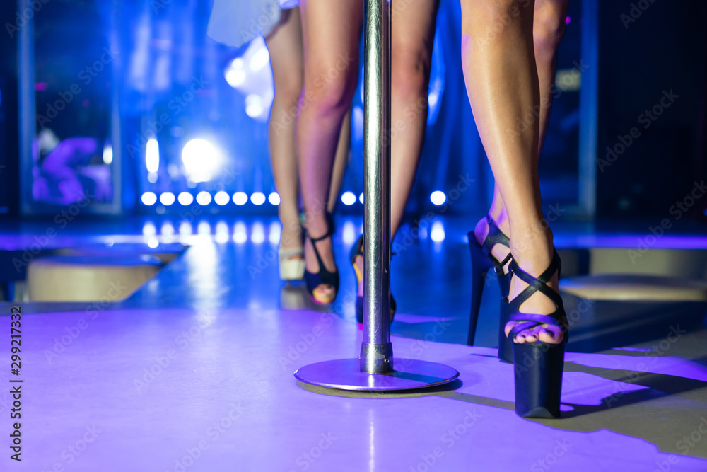 Fototapety, obrazy: Young sexy woman pole dancing striptease with pylon in night club. Beautiful naked stripper girl on stage. Beautiful female legs in high-heeled shoes strips