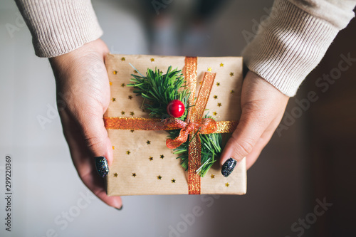 Fotomural  Young women with black glitter nails holding Christmas present box and showing it