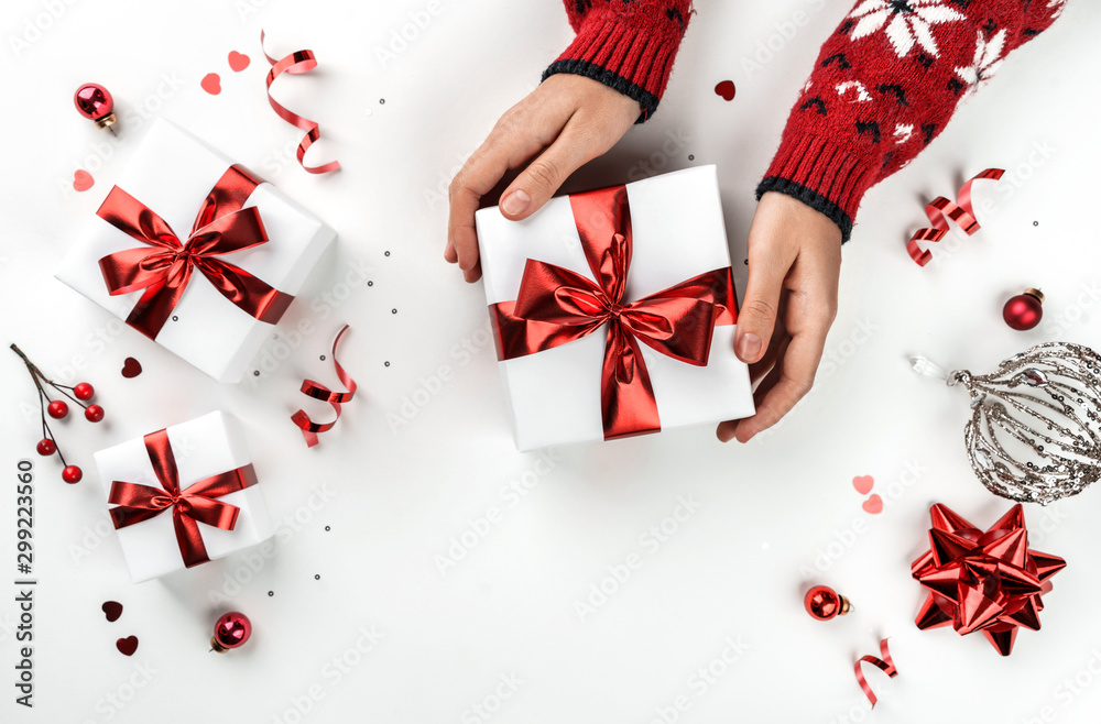 Fototapeta Female hands holding Christmas gift box on white background with fir branches, red decoration, sparkles and confetti. Xmas and New Year greeting card, winter holiday. Flat lay, top view
