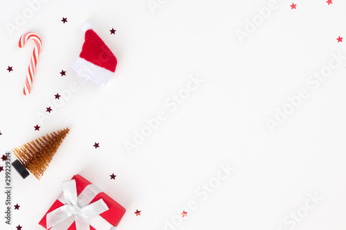 Fototapeta Red Christmas gift, Santa's hat, candy cane, golden fir on white background. Congratulation, Happy New Year concept. Top view, flat lay, copy space obraz na płótnie