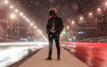 A Motorcyclist In Helmet Stands Among Many Lanterns. A Lot Of Light Effects. Middle Of The Light Street. Night City. Snowfall In The City.