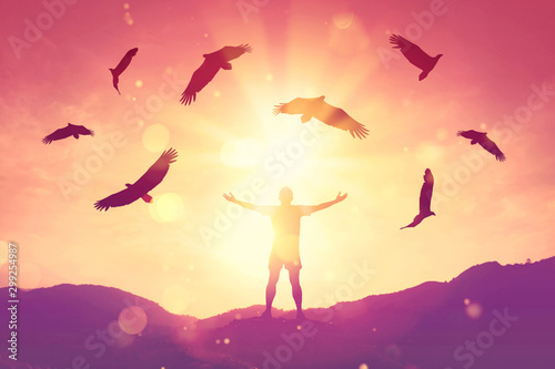 Poster Eagle Man raise hand up on top of mountain and sunset sky with eagle birds fly abstract background.