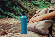 Hiker Man Sitting With Backpack And Bottle Of Water On Nature.