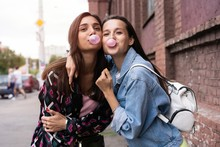 Two Young Beautiful Smiling Hipster Girls Blowing Bubble With Chewing Gum.