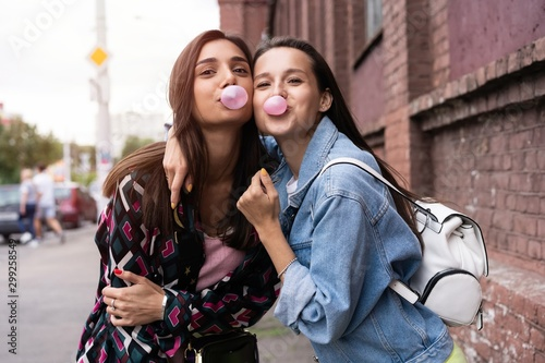 Two young beautiful smiling hipster girls blowing bubble with chewing gum Fototapet