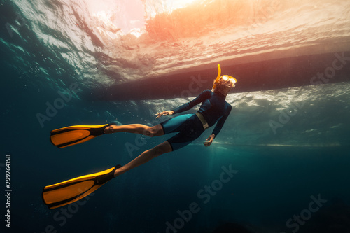 Fotografie, Obraz Woman freediver swims underwater under the boat