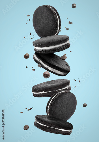 Falling chocolate cookies on color background