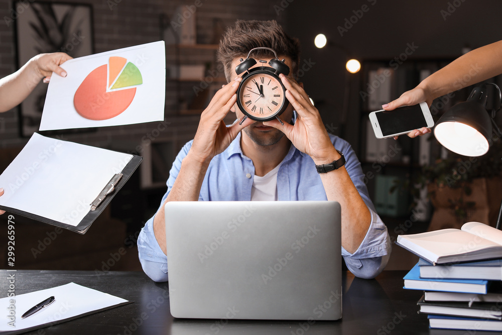 Fototapeta Young man with a lot of work trying to meet deadline in office