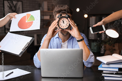 Young man with a lot of work trying to meet deadline in office Fototapeta