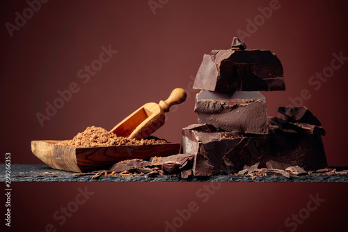 Black chocolate and wooden dish with cocoa powder on a brown background.