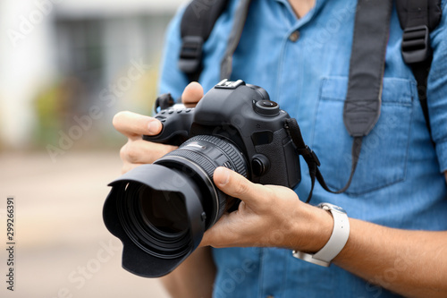 Young male photographer with camera outdoors, closeup Wallpaper Mural