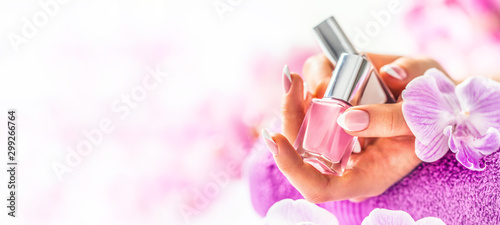 Autocollant pour porte Manicure Trendy nail manicure. Woman hands holding nails polishes. Pink decoration from orchids