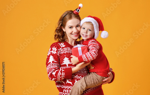 Photographie  happy family mother and child son with christmas gifts on yellow background