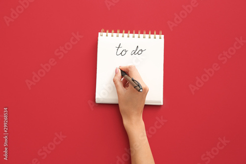 Photo  Woman making to-do list on color background