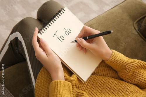 Photo  Woman making to-do list while sitting on sofa, closeup