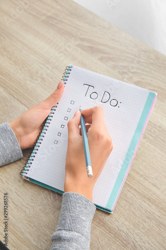 Woman making to-do list at table Wallpaper Mural