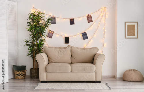 Interior of room with sofa and glowing garland with photos on white wall Tablou Canvas