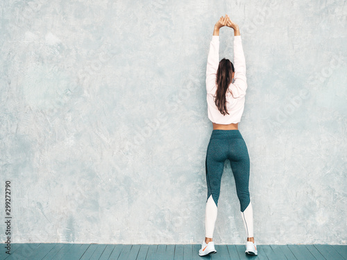 Back view of fitness woman in sports clothing looking confident Wallpaper Mural
