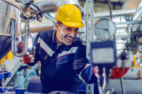 Fotografía  Handsome Caucasian blue collar worker in protective uniform and with hardhat on head checking on boiler while standing in factory