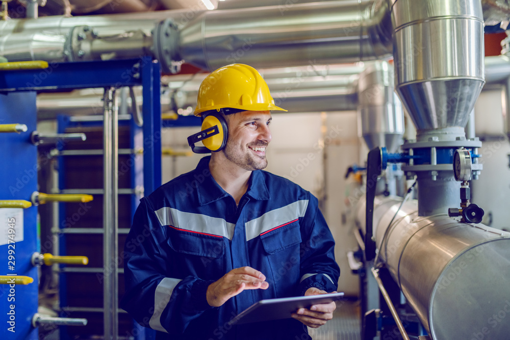Fototapeta Dedicated smiling factory worker standing next to boiler and holding tablet. Worker is dressed in protective uniform, having hardhat and antiphons.