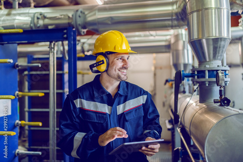 Stampa su Tela Dedicated smiling factory worker standing next to boiler and holding tablet