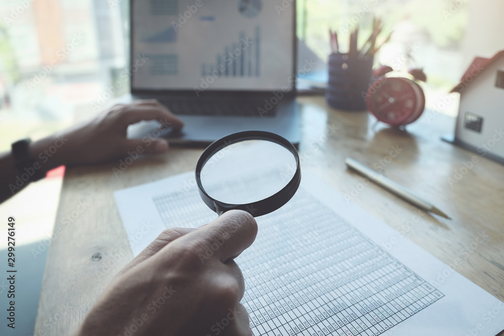 Fototapeta Business man using magnifying to review balance sheet annual with using  laptop computer to calculating budget. audit and Check integrity before investment concept.