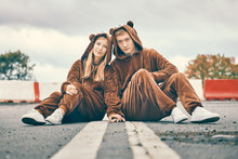Man And Woman In Bear Costumes Are Sitting On The Road. Young Couple Fights Hands. Concept Of Care, Love And Relationships