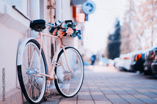 Tuinposter Fiets White bicycle with basket of flowers standing near the door on the street in city.