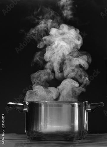 Fototapeta Steaming pot on black background. Smoke above boiling soup pot.  obraz