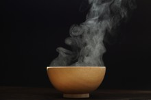 Bowl Of Hot Soup With Steaming On Wooden Table On Black Background. Hot Food Consept.
