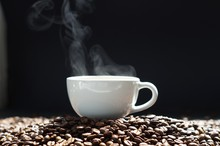 A Cup Of Hot Coffee With Steaming And Beans On Wooden And Black Background