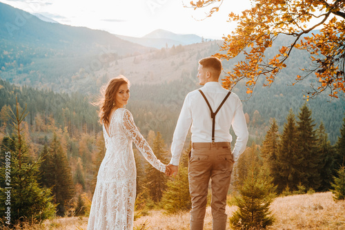 Elegant bride and groom walking in sun light holding hands, boho wedding couple