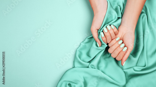 Autocollant pour porte Manicure Hands of a young girl on a mint silk cloth, manicure on a trendy background , green polish